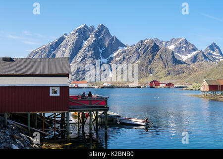 Stampen Cafe in red wooden building on stilts overlooking sea and mountains in fishing village of Sund, Flakstadøya - Stock Photo