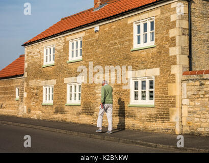 Old / senior man walking: Fit and trim elderly man taking brisk, daily walk in the warm, early morning sunshine, - Stock Photo