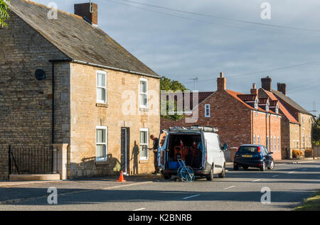 Tradesman cleaning the fragile window of an old stone house, using specialist, professional equipment. Langtoft, - Stock Photo