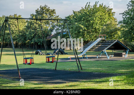 Children's playground / play park, with swings and slide, and nobody around, in the village of Langtoft, Lincolnshire, - Stock Photo