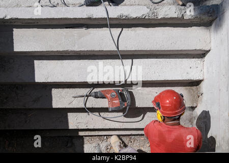 Construction worker wearing safety helmet and headphones uses a sander to sand the steps of a swimming pool - Stock Photo