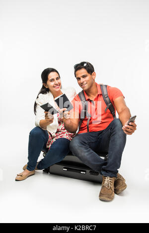 stock photo of indian young Couple packing for holiday, trying to close suitcase full with clothes, sitting isolated - Stock Photo