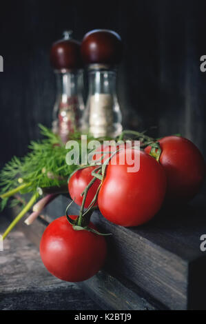 Ripe red tomatoes on a branch lying on a wooden background in rustic style, devices for spices in the bright light - Stock Photo