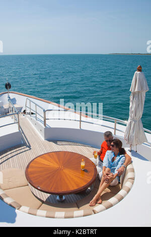 Couple relaxing aboard the yacht Glaze 161-foot Trinity in Miami, Florida, March 2011. - Stock Photo