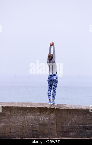 Young Woman doing yoga on sea wall in Cromer, Norfolk, UK. - Stock Photo