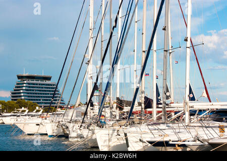 Vodice, Croatia - August 12, 2017: Sailing boats anchored in marina and luxury hotel Olympia Sky behind them - Stock Photo