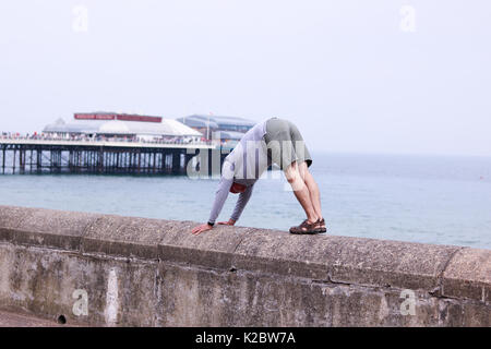 50 year old man doing a downward dog yoga pose on sea wall in Cromer, Norfolk, UK. - Stock Photo