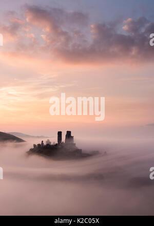 Corfe Castle at dawn with mist, Corfe Castle, Dorset, UK. September 2014. - Stock Photo