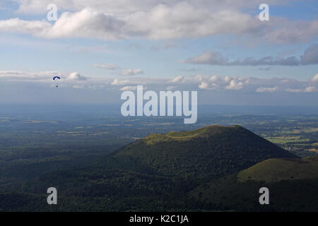 Paraglider flying over Puy Pariou Volcano,  Auvergne, Puy-de-dome, France, August. - Stock Photo