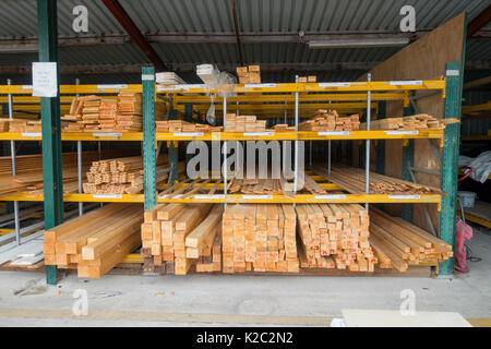 Stacked timber shelves at popular building trade merchants Travis Perkins outside under cover at Winsford Branch, - Stock Photo