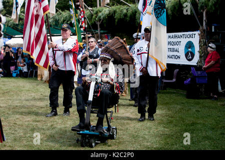 Stan Harris, the War Chief for the Mashantucket Pequot Tribal Nation, uses a scooter to participate in Grand Entry. - Stock Photo