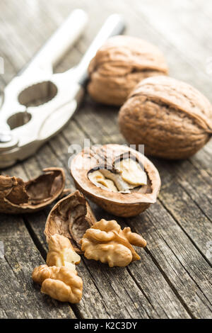 Cracked dried walnuts and nutcracker on old wooden table. - Stock Photo