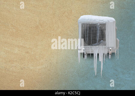 Frozen air conditioner with icicles. Heating and cooling concept. Vintage sand stone wall background. Toned photo. - Stock Photo