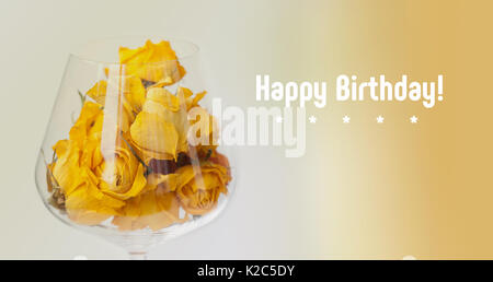 Happy birthday card. Dried rose flowers in wine glass, beige gradient background. yellow petals macro view, copy - Stock Photo