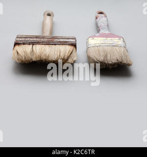Pair of used, aged paintbrushes on gray background. Painter brush texture, macro view,  copy space - Stock Photo