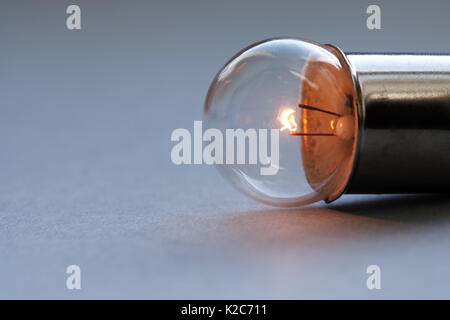 Vintage light bulb on gray background. Glowing filament close-up. Soft focus, copy space - Stock Photo