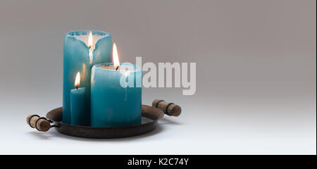 Romantic still life with turquoise different size candles on vintage metal plate. natural flame and drips. Beige - Stock Photo