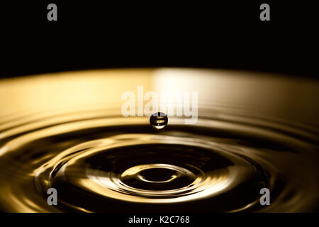 Dropping water bubble. Rings waves in dark bronze and black splashing background. macro view, soft focus, shallow - Stock Photo