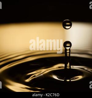 Water splashing. Dropping water bubble. Rings waves in dark bronze and black liquid splash. macro view, soft focus - Stock Photo