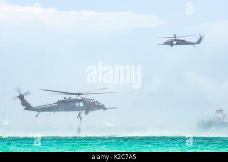 U.S. soldiers climb out of the water and into a U.S. Air Force HH-60G Pave Hawk helicopter during the National Salute - Stock Photo