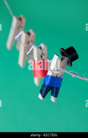 Creative design peg characters and clothesline. Man in suit, woman red dress. wooden clothespins on green background. - Stock Photo