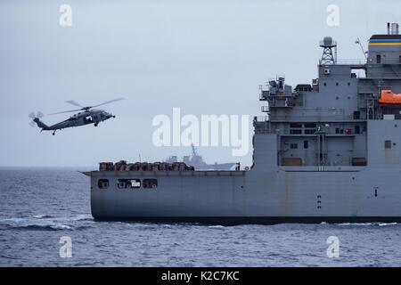 A U.S. Navy MH-60S Seahawk helicopter picks up supplies from the U.S. Navy Lewis and Clark-class dry cargo ammunition - Stock Photo