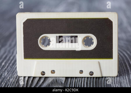 Vintage compact cassette with magnetic tape recording format for audio and playback. gray wooden background. Soft - Stock Photo