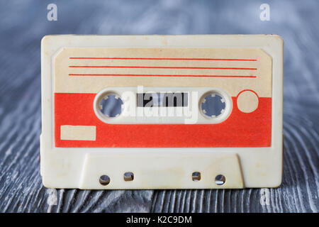 Red compact cassette with magnetic tape format for audio recording and playback. gray wooden background. Soft focus. - Stock Photo