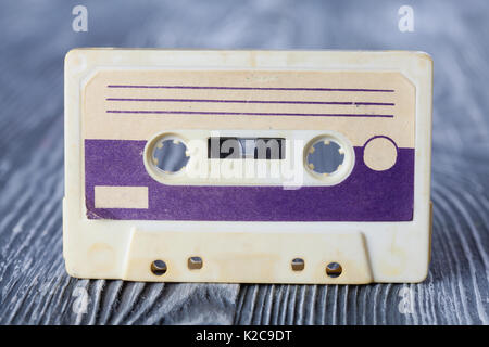 Violet compact cassette with magnetic tape format for audio recording and playback. MC on gray wooden background. - Stock Photo