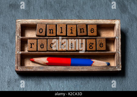 Online recharge concept. Vintage box, wooden cubes with old style letters, colorful red blue pencil. Gray stone - Stock Photo