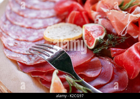 Italian antipasti and appetizers. board with slices prosciutto, salami, dried pork, salami ham with herbs. - Stock Photo