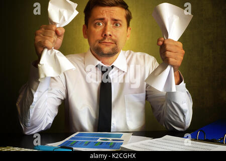 Nervous businessman observing bills. Problems in a business. - Stock Photo