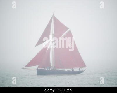 a single wooden pilot cutter classic yacht boat red sails sailing on calm water in misty fog foggy mist grey gray - Stock Photo