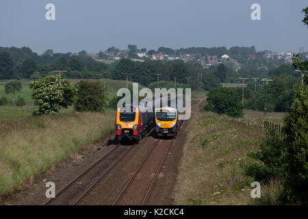 Virgin voyager train passes a First Transpennine express class 185 at Horwich Parkway (north of Bolton) - Stock Photo