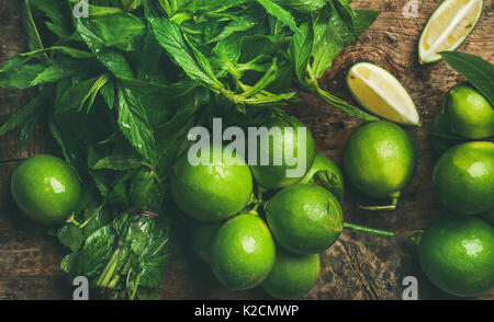 Flatlay of fresh limes and mint for making summer drinks - Stock Photo