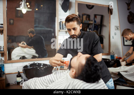 Hairstylist in black combing out bread for brunet at barbershop. - Stock Photo