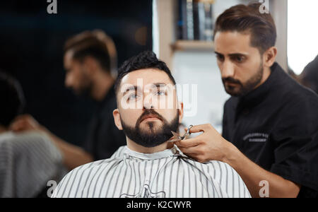 Hairdresser cutting bread with scissors for brunet man in barbershop. - Stock Photo
