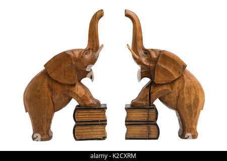 Two vintage old wooden carved brown elephants holders with raised trunks and opened mouth standing on books with - Stock Photo