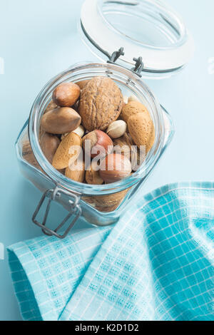 Different types of nuts in the nutshell in jar. Dried nuts. - Stock Photo