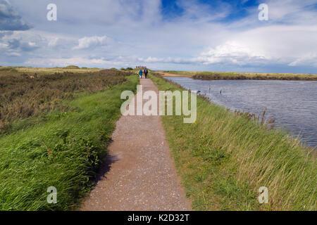 People walking along coastal path at at RSPB Titchwell Nature Reserve, Norfolk, UK, May 2015. - Stock Photo