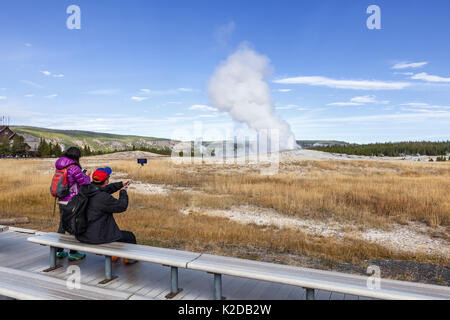 Tourists watching Old Faithful Geyser in Upper Geyser Basin, Yellowstone National Park, Wyoming, USA. September - Stock Photo