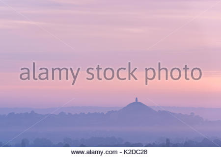 Distant Glastonbury Tor in mist at dawn, Somerset, England, UK. August 2013. - Stock Photo