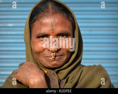 Elderly Indian Adivasi woman (Desia Kondh tribe aka Kuvi Kondh) with gold-and-gemstone nose jewellery and a tribal - Stock Photo
