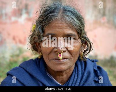 Elderly Indian Adivasi woman (Desia Kondh tribe aka Kuvi Kondh tribe) with gold-and-gemstone tribal nose jewellery - Stock Photo