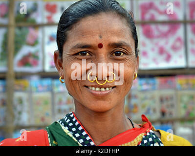 Middle-aged Indian Adivasi woman (Dongria Kondh tribe) with three golden nose rings, tribal earrings and red bindi - Stock Photo
