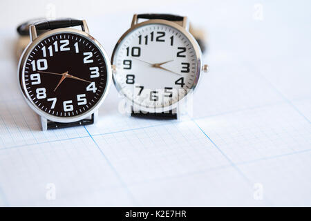 Pair of modern wristwatches standing on graph paper surface - Stock Photo