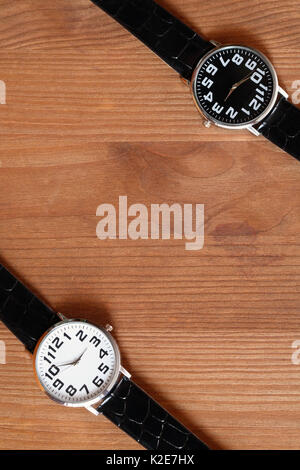 Pair of modern black and white wristwatches on wooden surface - Stock Photo