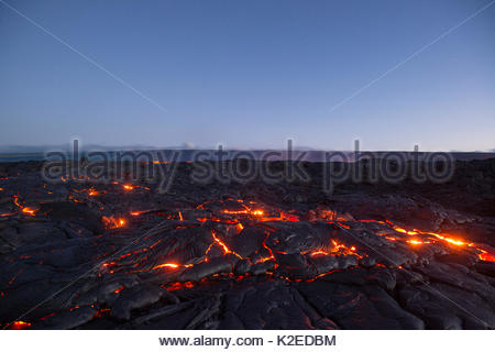 Hot lava glows through the cracks of pahoehoe in the 61G flow field, emanating from Pu'u O'o on Kilauea Volcano, - Stock Photo
