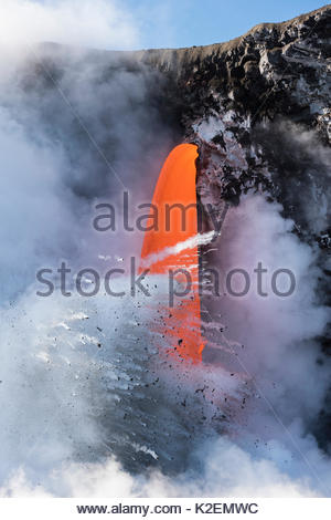 Hot lava from the 61G flow from Kilauea Volcano entering the ocean from the open end of a lava tube at the Kamokuna - Stock Photo