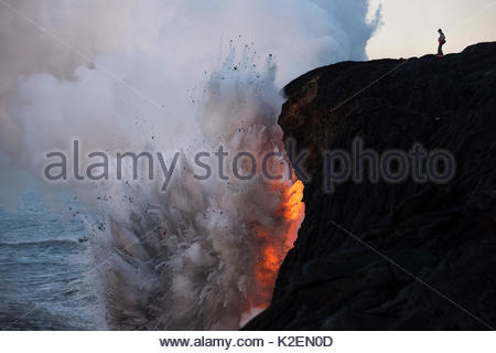 An unauthorized hiker in a restricted zone venturing out onto an unstable sea cliff over a lava tube where hot lava - Stock Photo